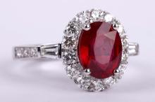 A glass filed ruby and diamond ring, The oval-cut glass filled ruby, within a surround of brilliant-cut diamonds, diamonds approx. 0.80ct total, stamped 750, ring size M