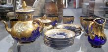 A suite of 20th Century Bohemian gilt overlay blue glass, comprising teapot, sugar bowl and cream jug, 7 cups and 8 saucers.