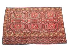An early 20th Century Turkoman Juval rug, 1.08m x 0.73, condition rating B.
