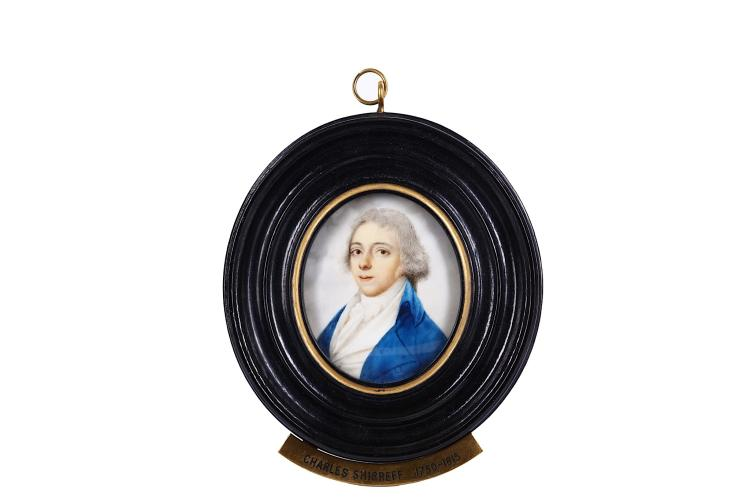 ATTRIBUTED TO THOMAS PEAT (BRITISH 1791-1831) Portrait miniature of a gentleman, in blue coat, white waistcoat and tied cravat, his hair powdered and worn en queue Watercolour on ivory Turned wood frame, brass plaque inscribed 'Charles Shirreff 1750-1815' Oval, 51mm high