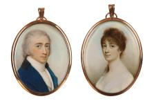 CHARLES ROBERTSON (BRITISH c.1760-1821)  A fine pair of portrait miniatures of a husband and wife, circa 1800, he in blue coat with black collar, white waistcoat and stock; she in white dress her brown hair upswept and plaited  Watercolour on ivory  In matching gold frames  Oval, 58mm high, a pair  (2)   Subject to CITES