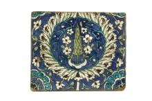 A DAMASCUS POTTERY TILE  16th-17th Century  Decorated in white, turquoise and green glaze on a blue background, with a central motif of a cypress tree and white flowers, encircled by a foliate garland,25cm x 21cm  Provenance:  Acquired from Monks of Kensignton Church Street in the 1950s.