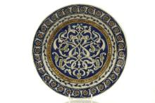 A QAJAR UNDERGLAZE-PAINTED POTTERY DISH IN THE IZNIK STYLE  Persia, 19th Century  Decorated with an arabesque interlace on a blue ground, 30.5cm diam