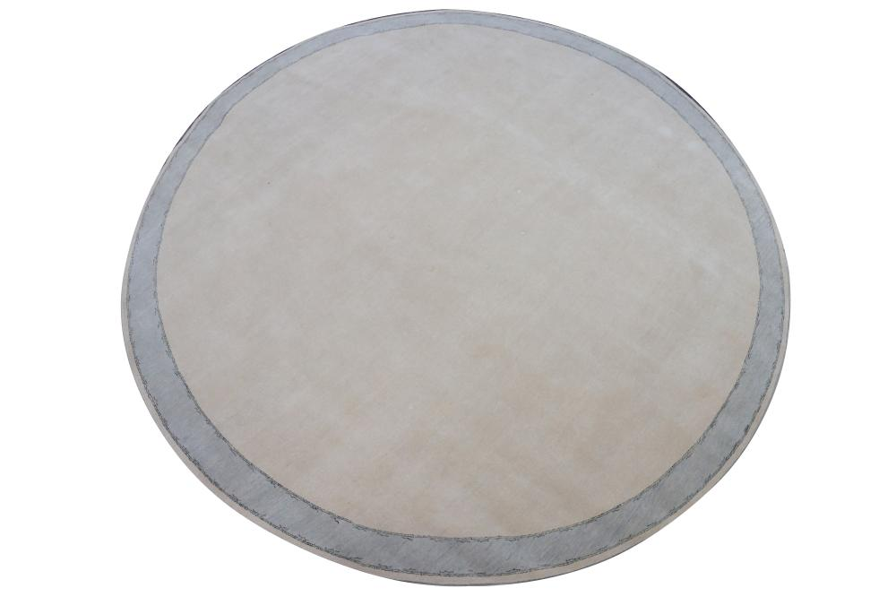 A large contemporary circular 100% wool carpet, light grey with a light blue border,