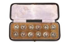 """A cased set of twelve Victorian antique sterling silver buttons, Birmingham 1900, by Levi & Salaman  Of circular form with an openwork depiction of a male figure dressed in the Antique manner amongst """"C"""" scrolls. (12)  Diameter – 2 cm/0.8 inches  Weight – 22 grams/0.7 ozt"""