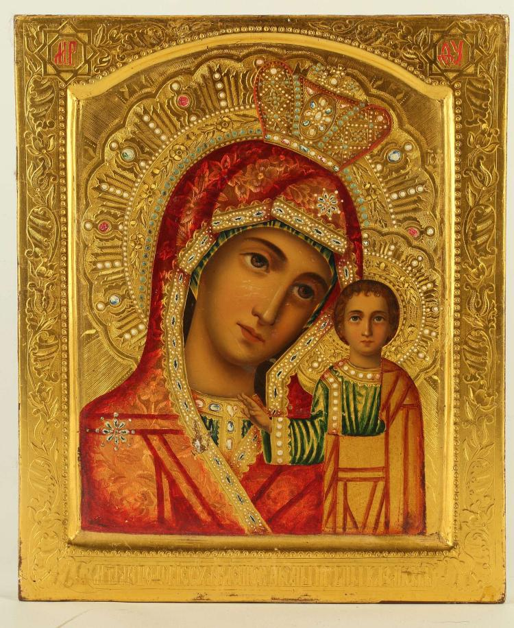 AN UNUSUAL RUSSIAN ICON: THE KAZAN MOTHER OF GOD, CIRCA 1890. Executed on a heavily gilded panel with arched and rounded kovcheg, the robe of the Virgin coloured in a translucent enamel type paint and colourfully painted with a profusion of faux gemstones. A unique icon, 9.5 x 11 inches.