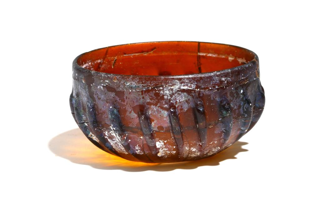 A ROMAN AMBER GLASS PILLAR-MOULDED BOWL