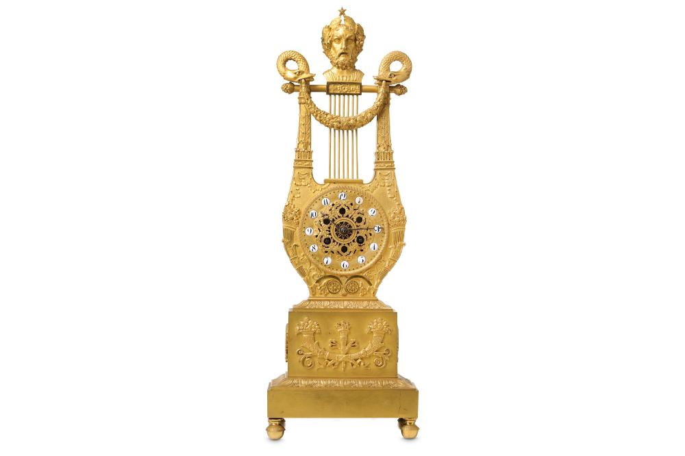 AN EARLY 19TH CENTURY FRENCH EMPIRE PERIOD GILT BRONZE LYRE CLOCK