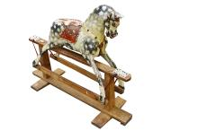 A small carved wood dapple grey rocking horse, early 20th century, with remnants of a leather saddle, on a pine safety frame, 102cm long x 86cm high