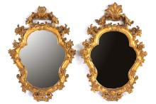 A pair of carved giltwood mirrors, 19th century, the frames of cartouche form, 44cm high x 31cm wide (2)
