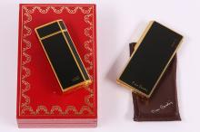 A Must de Cartier black lacquer lighter, signed and numbered, with associated Cartier box, and aPierre Cardin black lacquer lighter, signed (2)