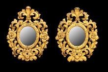 A pair of small early Florentine giltwood oval mirrors, 19th Century, with carved frames, 60cm high (2)