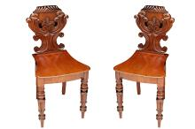 A pair of Victorian mahogany hall chairs, 19th Century, with carved backs and solid seats, on turned legs (2)
