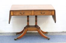 A Regency ebony strung mahogany sofa table, circa 1810, with canted rectangular twin flap top, fitted with two drawers, on four turned pillars, platform and downswept legs, 92cm wide