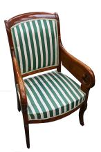 A French Empire-style mahogany armchair, 19th Century, upholstered in green and ivory striped fabric with open scroll arms, raised on carved sabre legs