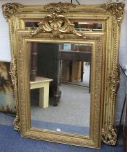 A large Victorian gilt framed mirror with swept corners, mirror size: 92 x 67cm, frame size: 124 x 97cm, sold with a further mirror in gilt frame with scalloped pediment, frame height: 120 x 76cm (2).