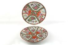 Very early 20th Century Chinese famille verte porcelain chargers, painted with panels of flora, fauna and figures in Oriental landscape, c.1900, 30cm diameter (2).