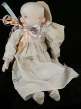 A porcelain headed doll having 3 faces, i.e. happy, sleeping or crying, 35cm high.