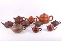 A collection of ten Chinese Yi Xing teapots with seal marks, some decorated with flowers, dragons and Chinese characters, some of the seal marks are: Gujianzhou, Jiang Rong, 7cm - 13cm high.