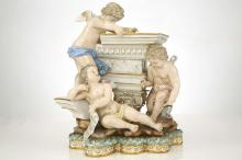 A MEISSEN PORCELAIN FIGURE GROUP EMBLEMATIC OF ARCHITECTURE, late 19th century, modelled as three winged putti working about a Corinthian column supporting a large capital, one holding a ruler, one a compass and book, the other a scroll, the rocky base applied with a stiff-leaf border entwined with ribbon, above a Vitruvium gilt scroll band, 22cm high, crossed swords mark in underglaze blue, impressed numbers 51 and 101   FOOTNOTES: An identical figure group was sold at Christie's, 12 March 2013, lot 331.