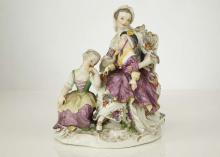 A MEISSEN PORCELAIN FIGURE GROUP, 19th century, modelled as a young lady wearing a floral dress, seated upon a high-backed rococo chair, a young boy in a purple gown on her knee, a girl seated upon a stool at her feet, raised upon a rococo scroll base encrusted with flowers and heightened in gold, 17.5cm high, crossed-swords mark in underglaze blue