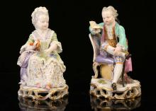 A PAIR OF MEISSEN PORCELAIN FIGURES OF CHILDREN, late 19th century, both modelled seated, he reading a book with a sword and tricorn hat at his side, a bunch of flowers at his feet, she holding a shell containing a pearl, wearing 18th century garb trimmed with lace, raised on pierced scroll bases heightened in gold, 13cm high, crossed swords marks in underglaze-blue, model no. C28 (2)