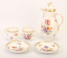 A BERLIN PORCELAIN PART COFFEE SERVICE, late 19th century, with neu-Ozier moulded borders, decorated with sprays and scattered sprigs of colourful flowers, heightened in gold, comprising a coffee pot and cover with twig handle and bud finial, 22cm high, together with two cups and saucers, the saucers 12.5cm diameter, sceptre marks in underglaze-blue, the coffee pot also with red printed orb above KPM (5)