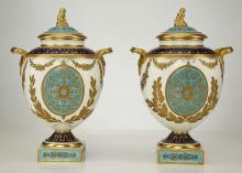 A FINE PAIR OF WEDGWOOD PORCELAIN NEOCLASSICAL VASES AND COVERS, late 19th century, both of twin-handled ovoid form raised on a square pedestal base, each side decorated with an oval medallion incorporating formal foliate motifs in gold on a turquoise ground, flanked by pairs of tooled gilt oak branches, all beneath garlands of flowers, the gilt handles with mask terminals, formal gold and blue borders to the shoulder and foot, the domed cover with a figural gilt finial, 29cm high, printed Wedgwood marks (2)