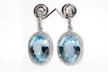 A pair of blue topaz and diamond pendent earrings  Each oval-cut blue topaz within a brilliant-cut diamond surround, suspended from a line of similarly-cut diamonds, mounted in 18 carat white gold, diamonds approx. 1.65cts total, UK hallmarks, length 3.4cm