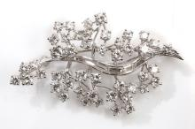 A diamond leaf brooch, circa 1965  The stem set with baguette-cut diamonds, flanked by clusters of brilliant-cut diamonds, diamonds approx.4.70cts total, numbered, length 5.1cm