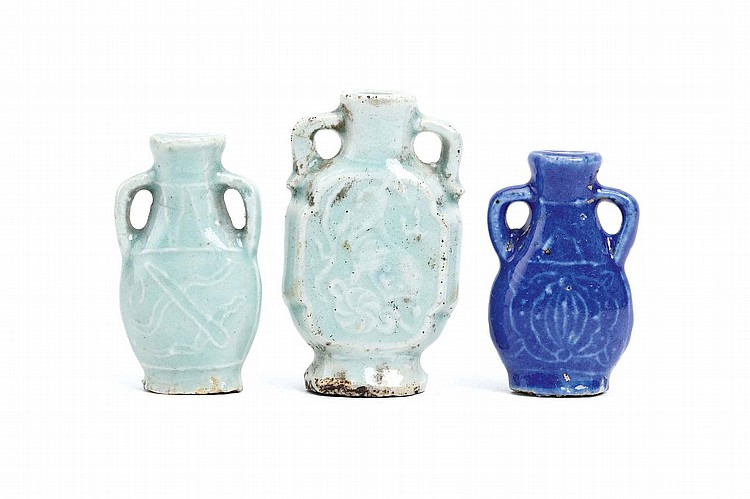 TWO CHINESE CELADON AND ONE BLUE-GLAZED SNUFF BOTTLE. Qing Dynasty. Each with looping handles on the shoulders, the bodies incised with designs, the largest vessel with a Buddhist lion dog chasing a ribboned ball, 7.5cm H. (3) Provenance: Collection of Bernard Buckman (1910 – 1991). ? ?????????????