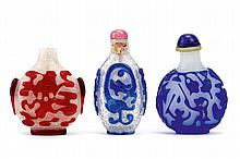 THREE CHINESE OVERLAY GLASS SNUFF BOTTLES.   Qing Dynasty.   Comprising a red overlay snowflake snuff bottle, a blue overlay snowflake 'chilong' snuff bottle and a red overlay 'monkey' snuff bottle, 6-7.5cm H. (3)   Provenance: Collection of Bernard Buckman (1910 – 1991).   ? ???????????