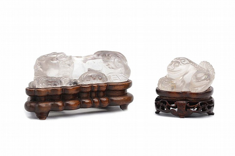 TWO CHINESE ROCK CRYSTAL BUDDHIST LION DOG CARVINGS.   Qing Dynasty.   The smaller seated with a ball, carved wood stands, 6cm long. (2)   Provenance: Collection of Bernard Buckman (1910 – 1991).   ? ???????