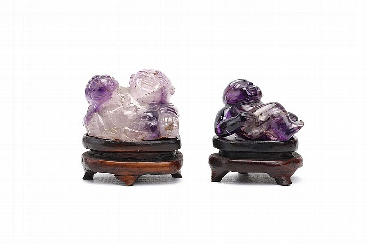 TWO CHINESE AMETHYST CARVINGS OF BOYS. Qing Dynasty. The larger representing Liu Hai, a three-legged toad on his back, the other as a reclining boy, wooden stands, 3cm H. (2) Provenance: Collection of Bernard Buckman (1910 – 1991). ? ????????