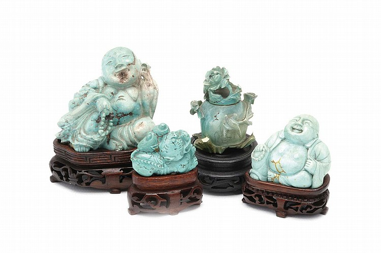 FOUR CHINESE TURQUOISE CARVINGS. 19th / 20th Century. Two carved as seated Buddhas, one miniature vase and cover carved in high relief as flowering branches, another carved as a tiger, wood stands, 3-5cm H. (4) Provenance: Collection of Bernard
