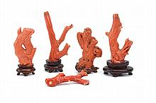 A COLLECTION OF FIVE CHINESE CORAL CARVINGS.   Qing Dynasty.   One carved as a bamboo branch with plum blossom, another as a sage, and three as stylised dragon creatures, 7cm H. (5)   Provenance: Collection of Bernard Buckman (1910 – 1991).   ? ??????