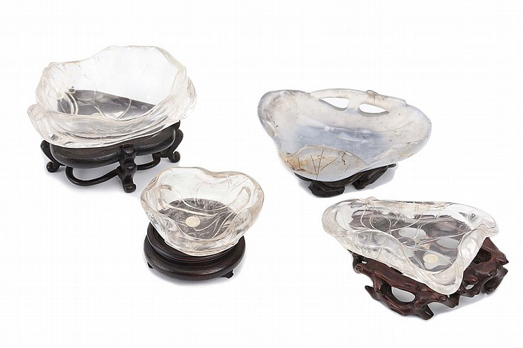 THREE ROCK CRYSTAL, AND ONE AGATE, 'LOTUS LEAF' WASHERS.   Qing Dynasty.   With carved and pierced wood stands, 7cm across. (4)   Provenance: Collection of Bernard Buckman (1910 – 1991).   ??? ?????????
