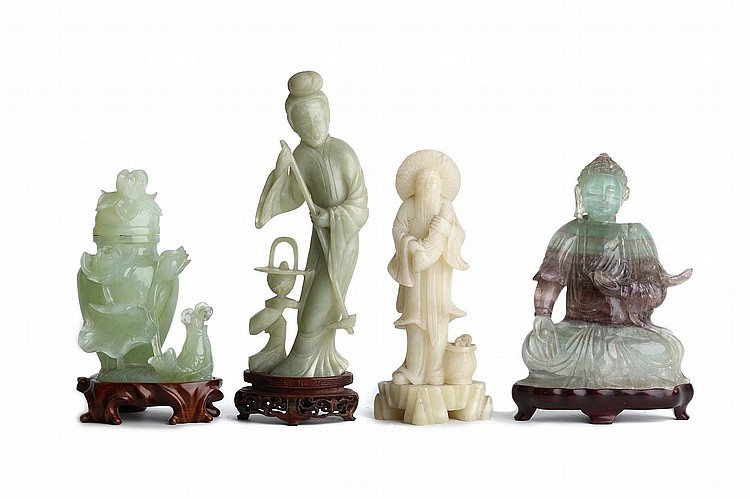 A GROUP OF FOUR CHINESE HARDSTONE CARVINGS.   19th / 20th Century.   Comprising of a jade carving of a lady beside a basket, an ornately carved vase and cover, with lotus leaves and a fish carved in relief, a carving of a fisherman, and a quartz figure of a seated Buddha, wood stands, 15-22cm H. (4)   Provenance: Collection of Bernard Buckman (1910 – 1991).   19-20?? ?????