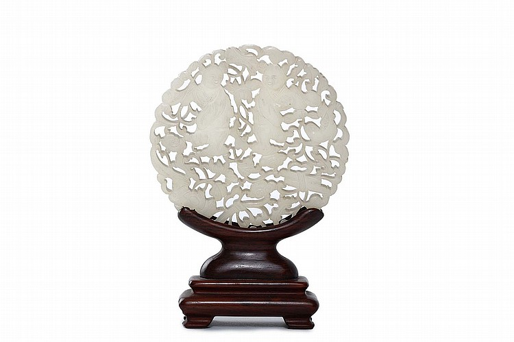 A CHINESE JADE CARVED AND PIERCED 'HEHE ERXIAN' CIRCULAR PLAQUE. Qing Dynasty, 18th / 19th Century. Carved on both sides with two boys among auspicious symbols, wood stand, 8.5cm diameter. Provenance: Collection of Bernard Buckman (1910 – 1991). ?18-19??  ????????