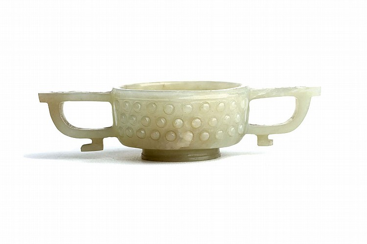 A CHINESE CELADON JADE ARCHAISTIC TWO-HANDLED CUP.   Qing Dynasty, 18th / 19th Century.   The rounded sides rising from a stepped foot to a lipped rim, flanked by a pair of handles, the exterior decorated with three horizontal rows of raised circular bosses, 2.5cm H, 5.5cm diameter.   Provenance: Collection of Bernard Buckman (1910 – 1991).   ?18-19??  ????????