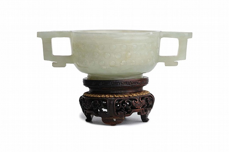 A CHINESE CELADON JADE ARCHAISTIC TWO-HANDLED CUP.   Qing Dynasty, 18th / 19th Century.   The rounded sides rising from a stepped foot to a lipped rim, flanked by a pair of handles, the exterior decorated with three horizontal rows of raised circular bosses, 7cm diameter, 4cm H.   Provenance: Collection of Bernard Buckman (1910 – 1991).   ? ????????