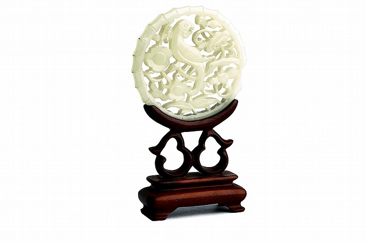 A CHINESE WHITE JADE 'PARROT' CIRCULAR PLAQUE. Qing Dynasty. Both sides carved with the parrot among scrolling foliage, prunus blossom, and lingzhi within a nodular bamboo stem border, wood stand, 6cm diameter. Provenance: Collection of Bernard Buckman (1910 – 1991). ? ????????? Literature: For a closely related carving see Marchant, Post-Archaic Chinese Jades, 1995, cat no 45 where it is stated that the parrot is often thought to represent a warning to wives cuckolding their husbands.