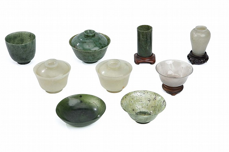 A COLLECTION OF CHINESE JADE CUPS SAUCERS, AND OTHER VESSELS.   Qing Dynasty, and later.   Comprising a pair of cups and cover, a spinach jade cup and cover, an agate bowl, a spinach jade brush pot, a pale celadon vase, and other vessels, 11cm diameter. (9)   Provenance: Collection of Bernard Buckman (1910 – 1991).   ???? ???????