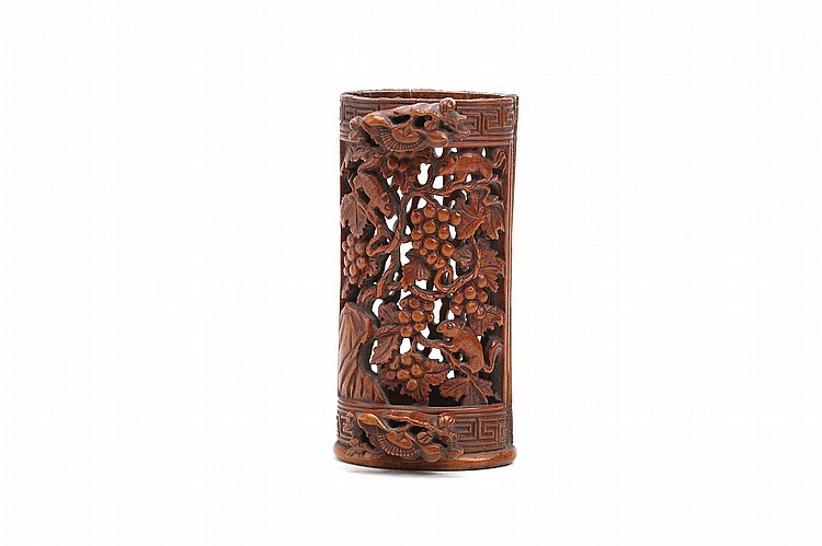 A CHINESE CARVED BAMBOO BIRD FOOD HOLDER.    Qing Dynasty, 18th / 19th Century.   The body carved and pierced with squirrels among grapes, with key-scroll borders at either end, two floral fasteners at either end, 8cm H.   Provenance: Collection of Bernard Buckman (1910 – 1991).   ?? 18/19??  ????????
