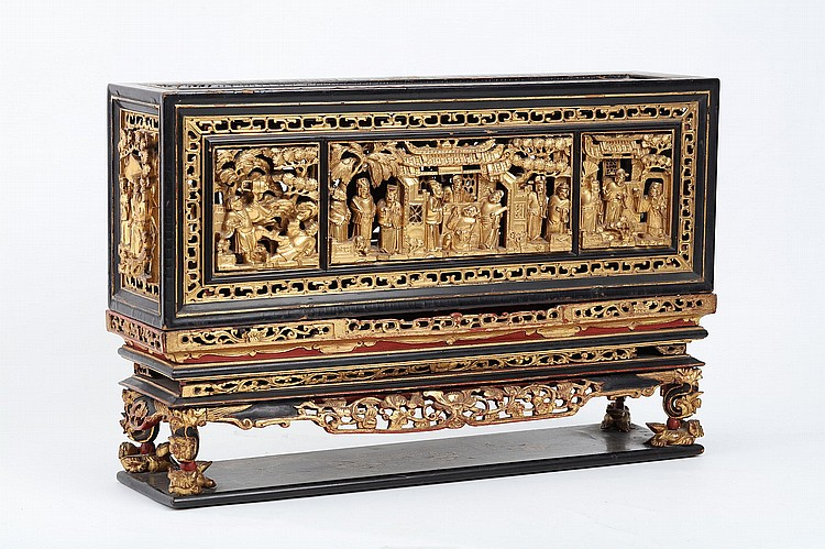 A CHINESE GOLD-PAINTED CARVED WOODEN RECTANGULAR BOX.   Qing Dynasty.   The four sides deeply carved and pierced with figurative scenes, the top with a lacquer painted scene, the box supported on four feet supported on Buddhist lion dogs, 29.5 x 45 x 12cm.   Provenance: Collection of Bernard Buckman (1910 – 1991).   ? ??????