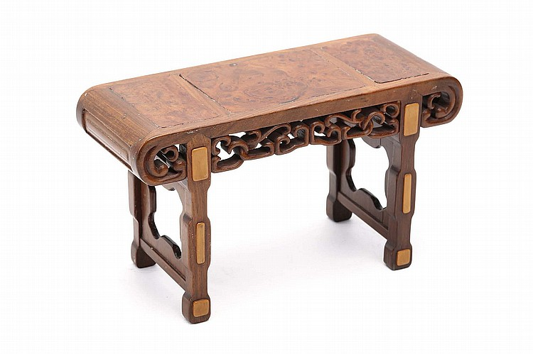 A CHINESE CARVED WOOD ALTAR TABLE FOR A HOUSEHOLD SHRINE. 19th / 20th Century. Of miniature form, the top inlaid with burl-wood panels, with pierced friezes on square-section end supports, 15cm H. Provenance: Collection of Bernard Buckman (1910 – 1991). ? ????????