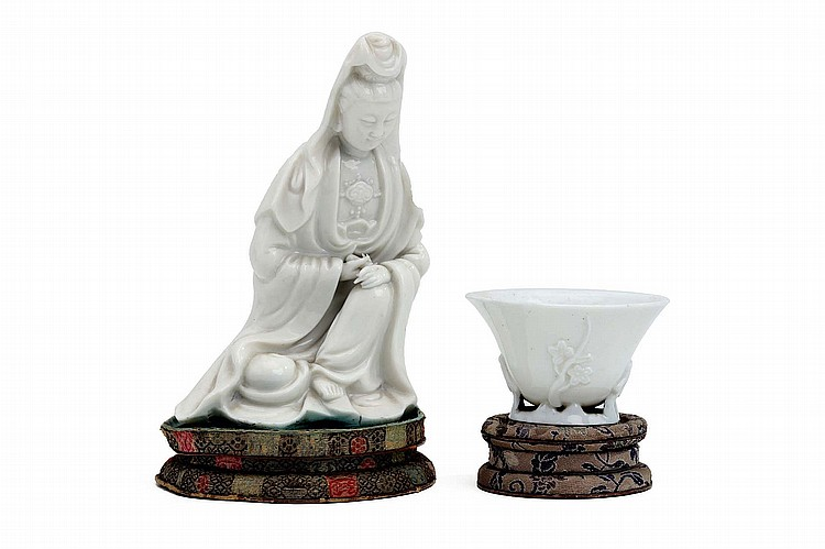 A CHINESE BLANC DE CHINE MODEL OF GUANYIN TOGETHER WITH A LIBATION CUP.   Qing Dynasty.   The Guanyin seated in long flowing robes with hands together and eyes downcast, the cup with flowering plum tree branches modelled up the body, each supported on a silk-mounted stand, 17cm H / 5cm H. (2)   Provenance: Collection of Bernard Buckman (1910 – 1991).   ? ????????