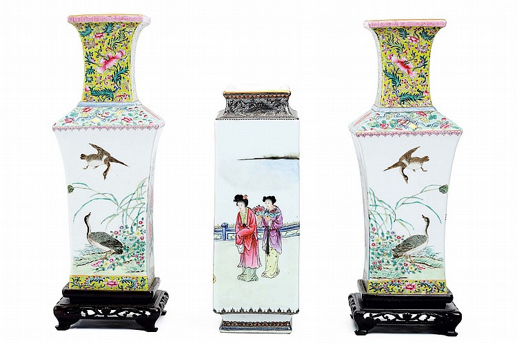 THREE CHINESE FAMILLE ROSE VASES OF RECTANGULAR SECTION.   20th Century.   Comprising a pair of vases, the bodies decorated with birds and flowers, with a band of scrolling flowers on a yellow ground to the base and neck, Qianlong nianzhi mark to base, wooden bases, together with a vase decorated with a continuous scene of ladies on a garden veranda, Da Qing Qianlong nianzhi mark to base, 32 / 29cm H. (3)   Provenance: Collection of Bernard Buckman (1910 – 1991).   20?? ????????
