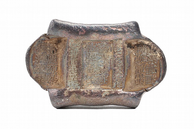 "A CHINESE SILVER INGOT.   Qing Dynasty.   Of rectangular form, with a recessed rectangular panel at the centre and recessed ears with rounded edges at each side separated by two ridges, impressed over the surface with Chinese characters, 1.5 x 6cm.   Provenance: Collection of Bernard Buckman (1910 – 1991).   ? ??""???? ???? ???????""?????"