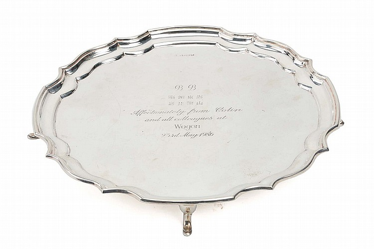 "AN INSCRIBED PRESENTATION SILVER SALVER. 1986. Of circular form with shaped quatrefoil border, on four feet, inscribed 'B[ernard] B[uckman]… Affectionately from Colin and all colleagues at Wogen, 23rd May 1986"", the tray by F Drury Ltd, Sheffield 1986, 30.5cm diameter, 793g. Provenance: Collection of Bernard Buckman (1910 – 1991). 1986 ??????"
